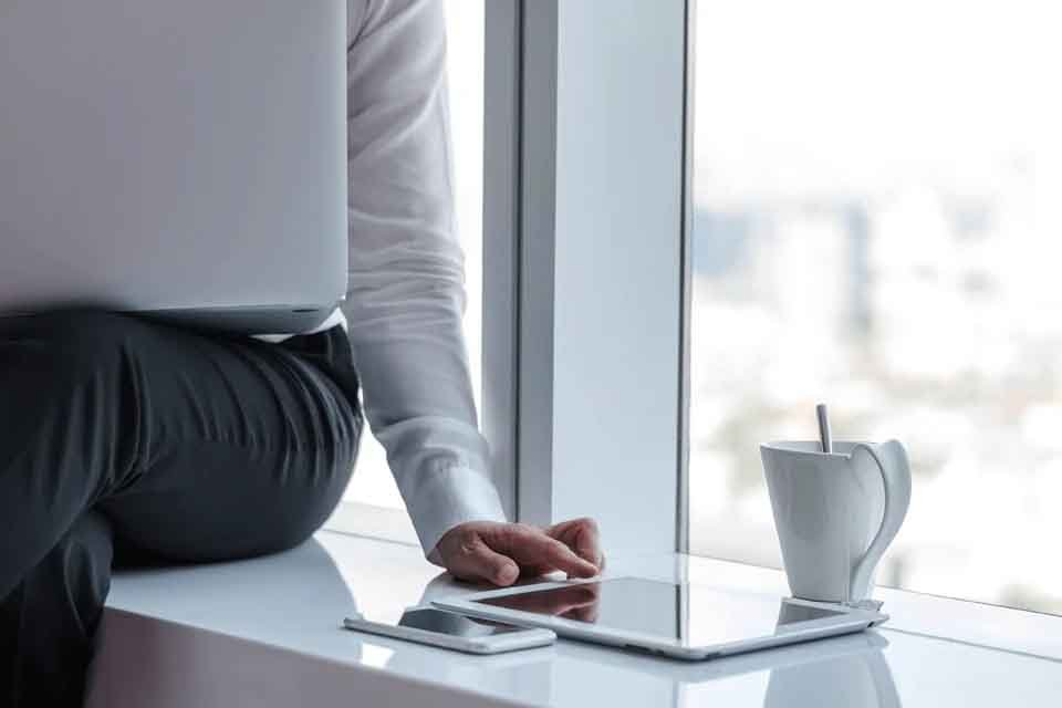 Businessman on the window side looking at his laptop and tablet with a cup of coffee.